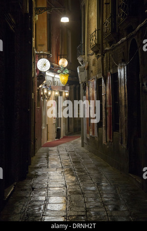 An image of a Venice back street at night after a rain shower. - Stock Photo