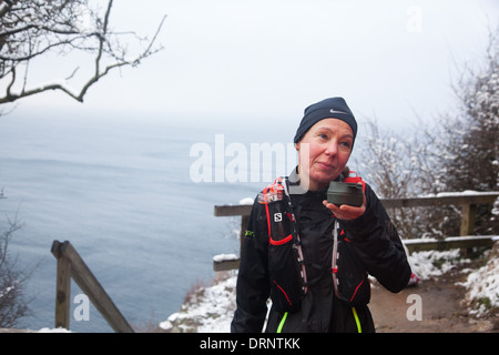 A runner has a drink and a brief break at the top of the stairs leading to Jons Kapel. - Stock Photo