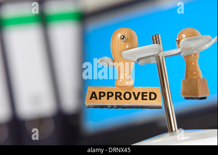 rubber stamp in office marked with approved - Stock Photo