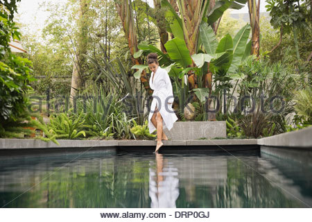 Woman dipping foot in swimming pool - Stock Photo