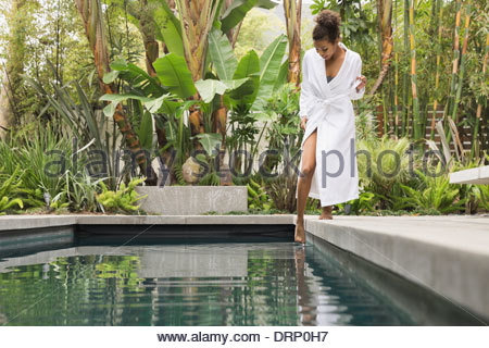 Woman dipping foot into swimming pool - Stock Photo