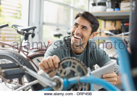 Cheerful man working in bicycle shop - Stock Photo