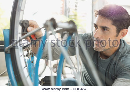 Man repairing bicycle in shop - Stock Photo