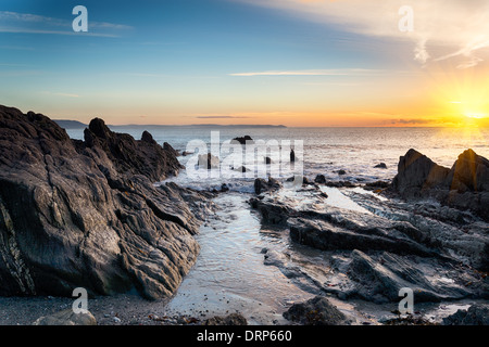 Sunrise at a rock beach at Looe in Cornwall - Stock Photo