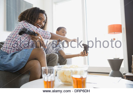 Siblings playing video games at home - Stock Photo
