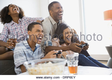 Family playing video games at home - Stock Photo