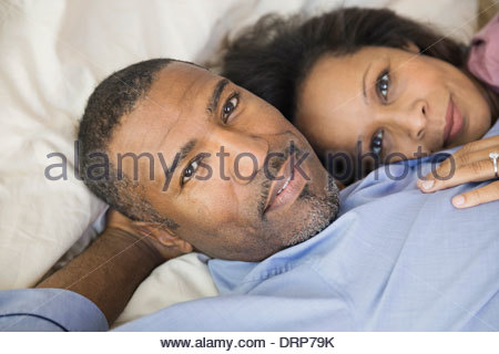 Portrait of couple resting in bed - Stock Photo