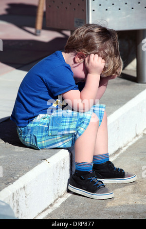 Small boy sitting on steps with head in hands - Stock Photo