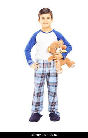 Full length portrait of a boy in pajamas holding teddy bear - Stock Photo