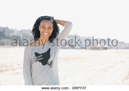 Smiling woman standing on beach - Stock Photo