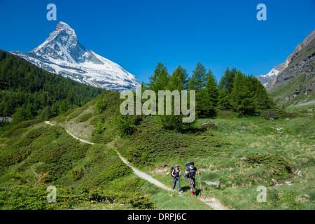Hikers on walking trail below the Matterhorn mountain in the Swiss Alps near Zermatt, Switzerland - Stock Photo