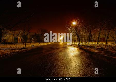 village street at cold winter night under lights - Stock Photo