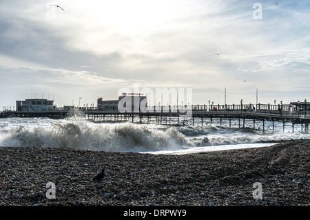 The pier with a deserted beach and stormy sea in winter, Worthing, West Sussex, England, UK. - Stock Photo