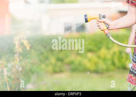 Lifestyle summer scene. Woman watering garden plants with sprinkler. - Stock Photo