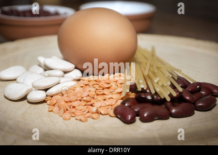 A still-life study of an egg, beans,pasta and red lentils. - Stock Photo