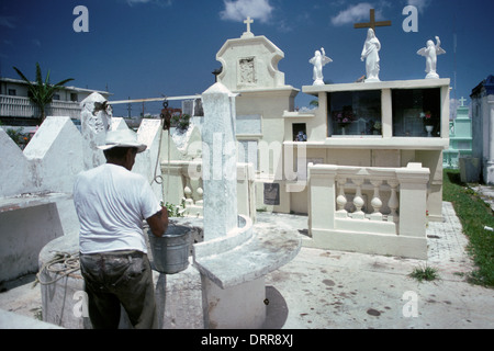 Man drawing water from well in cemetery in Cozumel, Mexico - Stock Photo