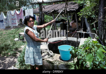 Woman drawing water from a well in Cozumel, Mexico - Stock Photo