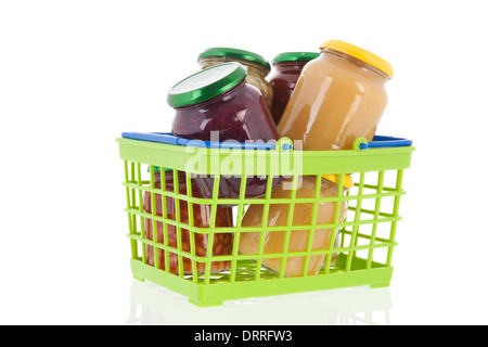 Preserved vegetables in glass pots in shopping basket - Stock Photo