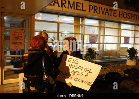 Dublin, Ireland. 31st January 2014. Protester stand outside Mount Carmel Hospital talking, holding a sign that reads - Stock Photo