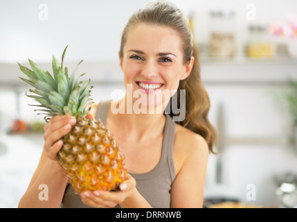 Happy young woman showing pineapple - Stock Photo