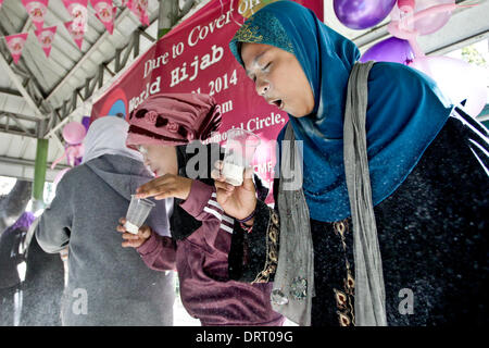 Quezon, Philippines. 1st Feb, 2014. Muslim and non-Muslim women participate in a game blowing flour out of a plastic - Stock Photo