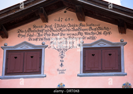 Window shutters, inscription and paint effects on 18th Century house built 1765 in Klosters, Graubunden, Switzerland - Stock Photo