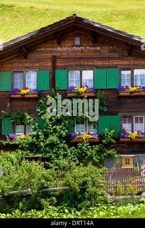 Typical Swiss wooden Alpine chalet style house with inscription in Klosters in Graubunden region, Switzerland - Stock Photo