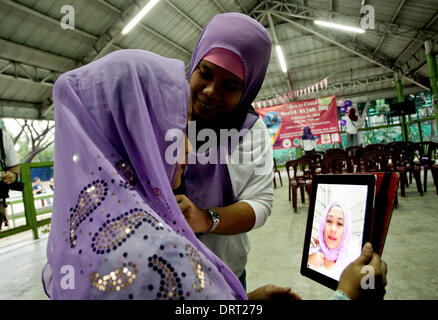 Quezon, Philippines. 1st Feb, 2014. Dr. Claire Bermundo a Catholic fits her Hijab during the World Hijab day in - Stock Photo