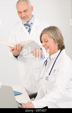 Medical team doctors read book look computer - Stock Photo