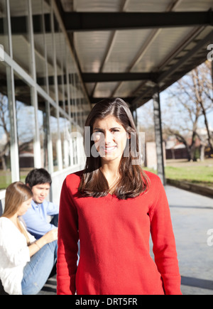 Woman Smiling With Students In Background On Campus - Stock Photo