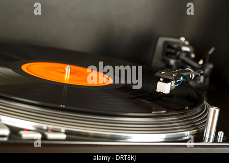 Turntable rotates together with vinyl record on - Stock Photo