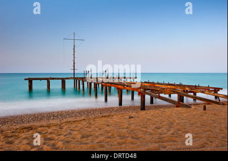 rusty skeleton of the old pier and turquoise sea - Stock Photo