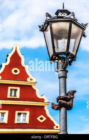 One of Wroclaw's famous little bronze gnomes, dwarfs or krasnale statues climbing a streetlight in the old town - Stock Photo