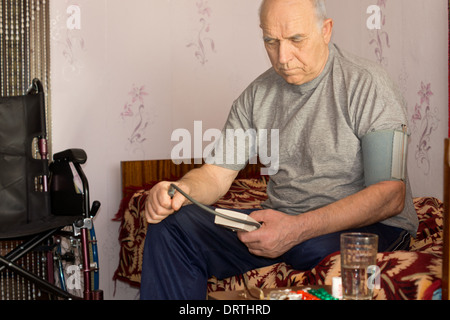 Senior disabled man taking his own blood pressure sitting on his bed alongside his wheelchair using a pressure cuff - Stock Photo
