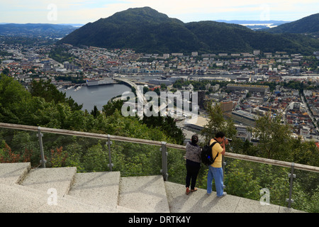 Man photographs Bergen city from Mount Fløyen, Norway - Stock Photo