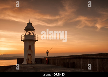 Lighthouse and breakwater in the coastal fishing port of Brixham, South Devon with a pleasure fisherman taken at - Stock Photo