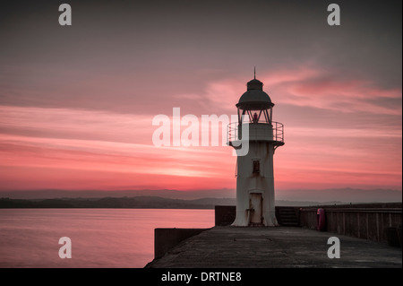 Lighthouse and breakwater in the coastal fishing port of Brixham South Devon taken at sunset. - Stock Photo