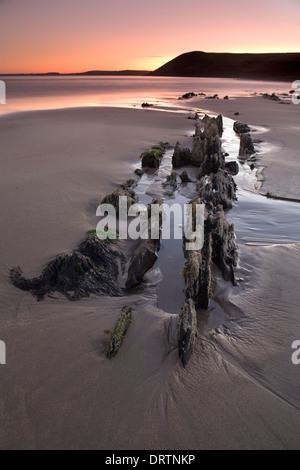 Jagged rocks sticking out of the sand at low tide during sunset on Manorbier beach, Pembrokeshire, South Wales, - Stock Photo