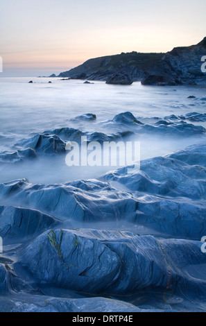 The blue rocks on the beach at Dollar Cove, Cornwall, are being covered by the incoming tide at sunset. The long - Stock Photo