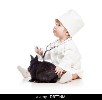 Baby playing doctor with pet bunny - Stock Photo