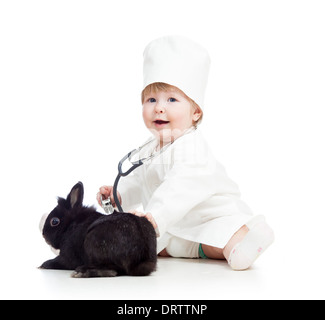 kid with clothes of doctor playing with pet bunny - Stock Photo