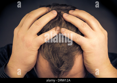A depressed man with his hands over his face - Stock Photo