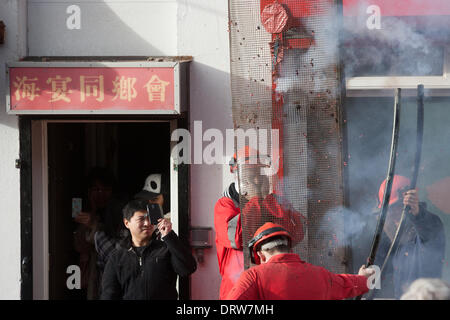 Liverpool, UK. 2nd Feb 2014. A man films technicians setting off firecrackers in Liverpool's Chinatown during Chinese - Stock Photo