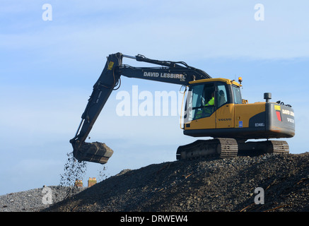 A digger working on a shingle bank - Stock Photo
