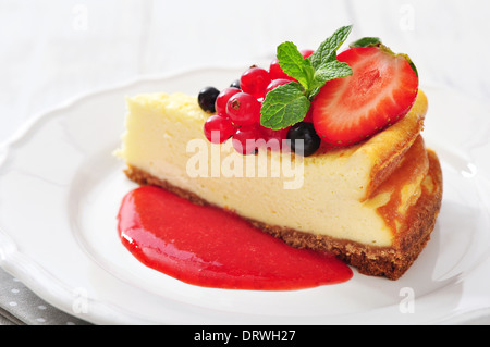 Cheesecake with fresh berries and mint on plate closeup - Stock Photo