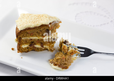 Homemade carrot cake on a white serving plate. - Stock Photo