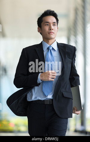 Young Chinese businessman running in a modern city street - Stock Photo