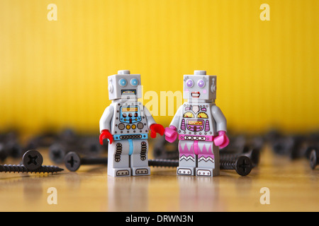 Grey male and female toy Lego robots surrounded by screws. Yellow background, wood floor - Stock Photo
