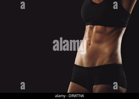 Slim and fit woman belly. Torso of fitness female. Mid section of woman body with muscular abs on black background - Stock Photo