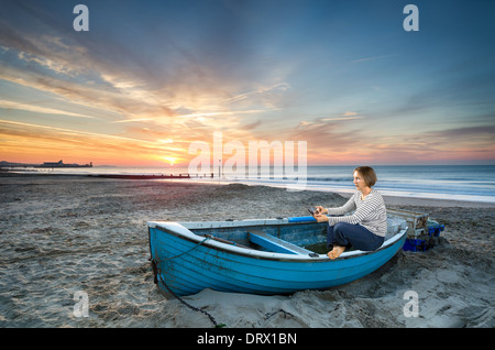 Mature woman in 50's using tablet device at sunrise on an idyllic beach - Stock Photo